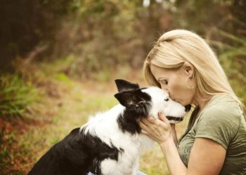 Девушка целует собаку